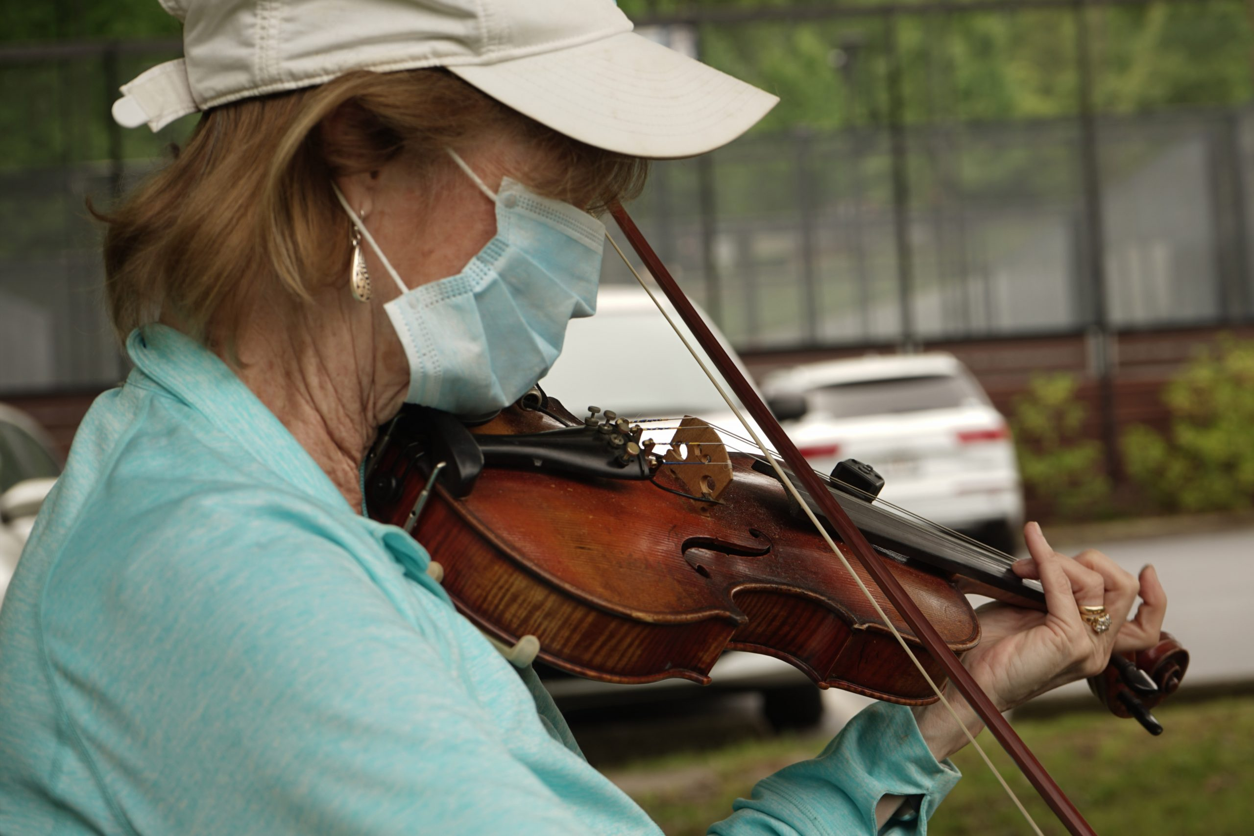old woman wearing mask playing violin hat